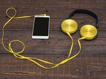Gadgets for every day ready for their work. Headphones and smartphone - gadgets for every day Royalty Free Stock Photo