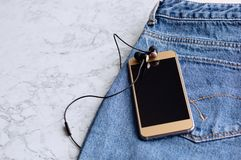 Headphones and smartphone in the pocket of jeans, close-up stock images