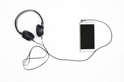 Headphones with smartphone on a white background. Royalty Free Stock Image
