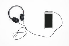 Headphones with smartphone on a white background. Stock Photo