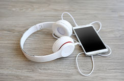 Headphones and smartphone on wooden Royalty Free Stock Photography