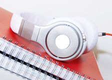 Headphones and Spiral  notebook on the desktop Royalty Free Stock Photos