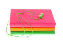 Headphones and stack of multicolored books on a white background Royalty Free Stock Image
