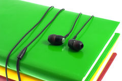 Headphones and stack of multicolored books on a white background Stock Images