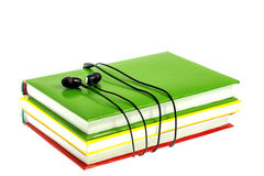 Headphones and stack of multicolored books on a white background Stock Image