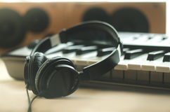 Headphones are on the synthesizer. The headphones are on the synthesizer. The synthesizer stands on the background of the speakers. Light photo. Front view stock photography