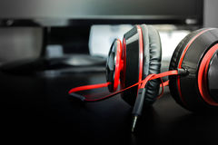 Headphones on the table in front of monitor. Gamepad  and  headphones lie against the backdrop of the monitor Royalty Free Stock Photo
