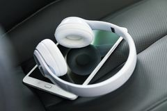 Headphones and tablet computer on the car seat. Modern wireless internet technology concept: macro view of tablet computer PC and white wireless headphones on royalty free stock photo