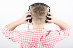 Headphones. Teenager listens music with headphones on light background, rear view Stock Photography