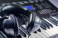 Headphones on top of a synthesizer buttons Stock Photo