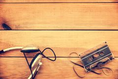 Headphones and translucent audio cassette tape on vintage wood planks  background. With copy space Royalty Free Stock Photo