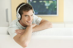 With Headphones and TV. Young man listening to music with headphones at home Stock Photos