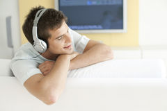 With Headphones and TV. Young man listening to music with headphones at home royalty free stock images