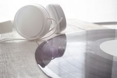 Headphones and vinyl disc on a white wooden table. Empty copy space for Editor`s text stock photos