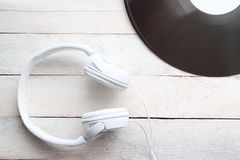 Headphones and vinyl disc on a white wooden table, top view. Empty copy space for Editor`s text stock photo