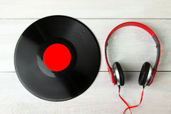 Headphones and vinyl. Full-size wired headphones near vinyl record on white wooden background Stock Image