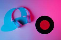 Headphones with vinyl record. 80s. Retro wave, neon light, ultraviolet. Top view, minimalism royalty free stock photo