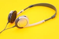 Headphones on yellow. Comfortable high-quality headphones silver on Headphones on yellow Royalty Free Stock Photos