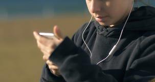 Headphones on young adult model woman girl portrait puts headphones to her ears stock video footage