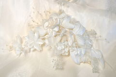 Headpiece White. Headpiece of silk flowers lying on back of gown Royalty Free Stock Image