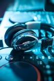 Headpones do DJ no controlador de mistura na luz de turquesa closeup Imagens de Stock Royalty Free