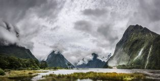 Heads in the Clouds Panorama at Milford Sound. `Heads in the Clouds` Panorama at Milford Sound with the clouds engulfing the mountain peaks - Panoramic view with royalty free stock images