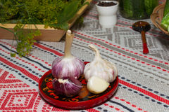 The heads of garlic on a plate made of wood. plates painted in K Royalty Free Stock Image