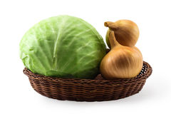 Heads of the green cabbage and gold onion in basket Royalty Free Stock Photo