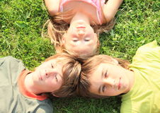 Heads of kids. Heads of two boys and one girl - smiling kids lying on green grass royalty free stock photos
