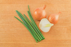Heads and leaves of onions. On a wood background Stock Photo