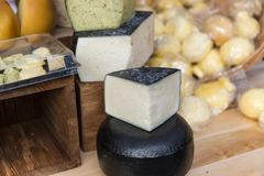 Heads of natural organic homemade cheese on the market. Stock Photography