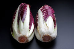 Heads of Red Radicchio. Two heads of red radicchio over black background royalty free stock photos