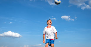 Heads in soccer. Happy boy playing football on sky background royalty free stock photo