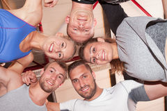 Heads together. Fitness team in a gym smiling to camera stock photos