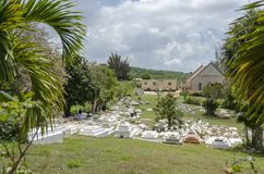 Small Cemetery Landscape. The heads of white tombs with tombstones on, in a small cemetery between trees, beside a small church. It is a cloudy day with thick stock image