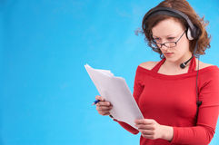 Headset. Young businesswoman in red dress on blue background Royalty Free Stock Photos