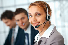 With Headset. Closeup of a businesswoman with headset, her colleagues at the background Stock Photo
