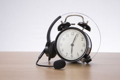 Headset coiled over a retro alarm clock stock photography