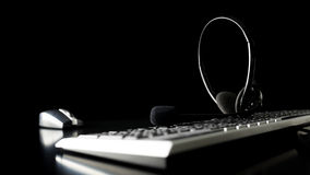 Headset on a computer keyboard. In a dark office at night with copyspace conceptual of a call centre, client services, telemarketing or customer support Royalty Free Stock Photography