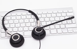 Headset with Keyboard. Office headphones with microphone over white keyboard on desk Royalty Free Stock Image
