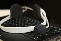 Headset on laptop. Black and white headphones with microphone lie on keyboard close up Royalty Free Stock Photos