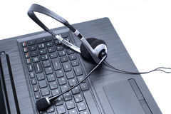 Headset lying on a laptop computer keyboard Royalty Free Stock Photography