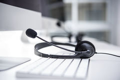 Headset with microphone on computer keyboard Royalty Free Stock Image