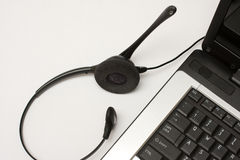 Headset next to laptop. Telephone operator headset next to laptop possibly working from home Royalty Free Stock Photo