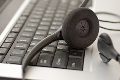 Headset next to laptop. Telephone operator headset next to laptop possibly working from home Royalty Free Stock Image