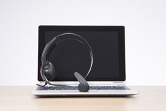 Headset on an open laptop keyboard royalty free stock photography