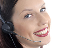 Close up of female call center telephone worker, headset, smiling, looking at camera Royalty Free Stock Photo