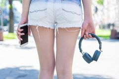 Headset without wire concept. Rear back behind cropped close up view photo of jeans denim mini shorts slim slender fit legs hips royalty free stock photo