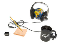 Headset on world globe with coffee and pencil isol Royalty Free Stock Photo