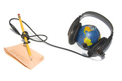 Headset on world globe with pencil and note isolat Stock Photo